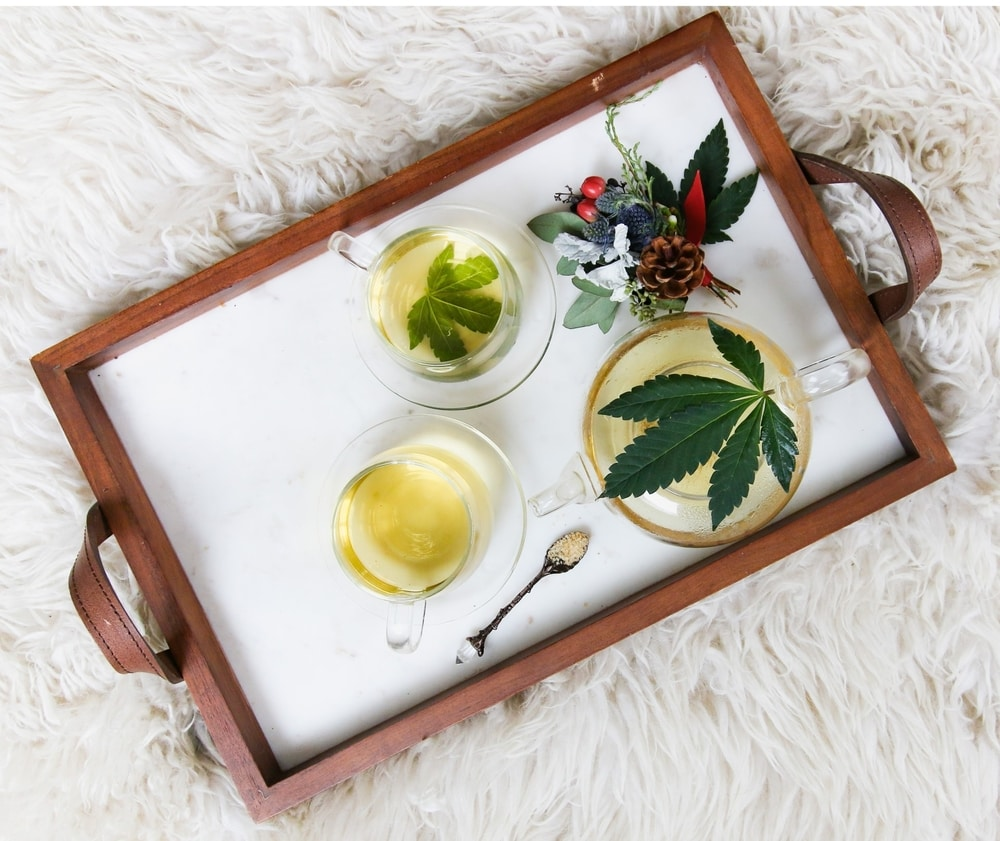 Cannabis tea cups and tea pot on tray