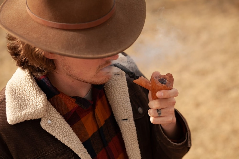 Cowboy smoking a wooden pipe in the desert